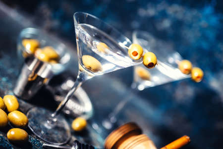 martini glass: Glasses of martini with olives and vodka. Alcoholic beverages served at bar Stock Photo