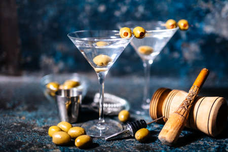 Martini cocktail drink with olives garnish and tools on rusty background 스톡 콘텐츠