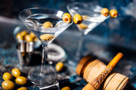 martini glasses: Martini, classic cocktail with olives, vodka and gin served cold in a restaurant Stock Photo