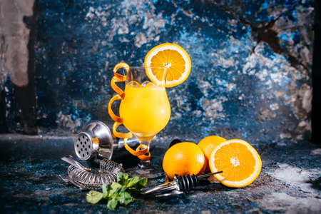 alcoholic drink: orange soft long drink, alcoholic beverage with tools and abstract background