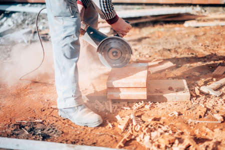cut off saw: Industrial construction worker using a professional angle grinder