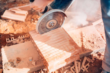 cut off saw: close-up details of worker using angle grinder for cutting bricks on construction site