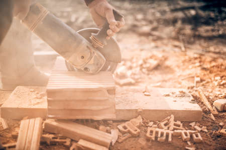 cut off saw: Industrial worker on construction site, working in debris and dus, sawing and chopping bricks with angle grinder Stock Photo