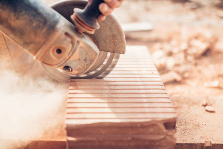 cutting through: Construction details - close-up of angle grinder cutting through bricks