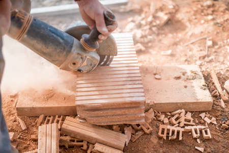 cut off saw: Construction worker using an grinder for cutting and sawing construction bricks