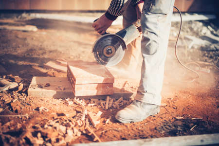 cut off saw: worker using an angle grinder on construction site for cutting bricks, debris. Tools and bricks on new building site