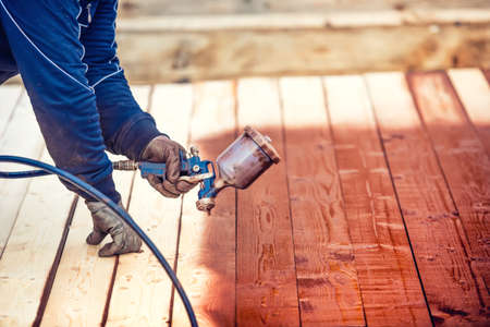 airgun: Industrial worker spraying paint over timber wood. Construction worker with spray gun