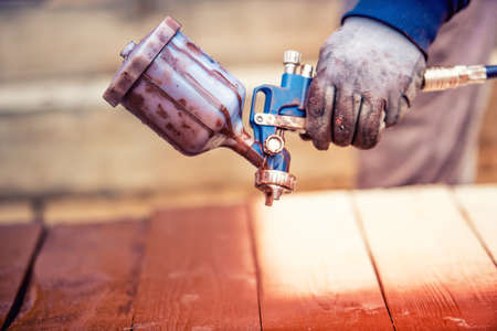 close-up of spray gun getting paint over timber. Young painter renovating Stock Photo