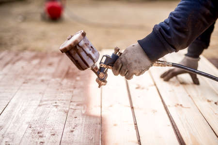 Primer plano de la mano del trabajador usando la pistola y la madera de la pintura