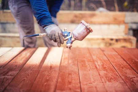 carpintero: personal de mantenimiento industrial, construcción pintura trabajador con pistola de pulverización en el sitio