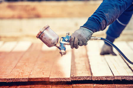 Man using protective gloves painting wooden timber with spray paint gun Foto de archivo
