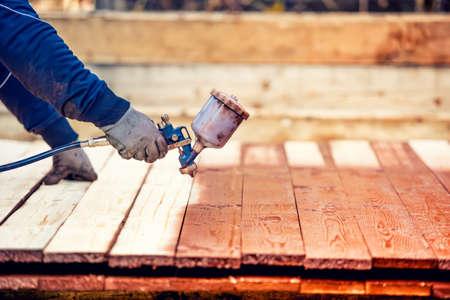 pulverizador: Hombre pintando la madera de color marrón, la renovación de la cerca de madera exterior. Trabajador que usa la pistola de pulverización
