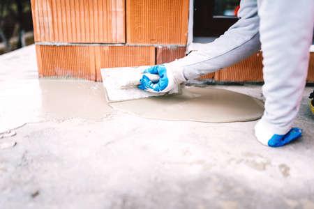 waterproofing material: industrial worker waterproofing part of house exposed to rain Stock Photo