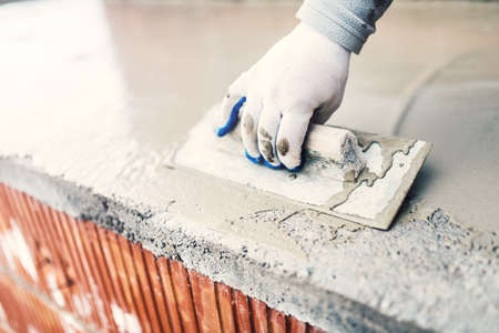 patching: protective material against water on house building. worker waterproofing cement Stock Photo