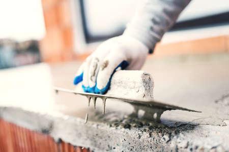 waterproofing material: construction worker using steel trowel for plastering