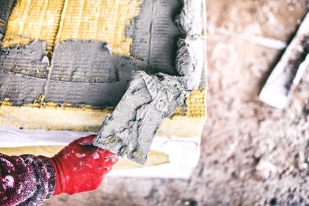 rock wool: close-up of worker hand on industrial construction site using a trowel and applying adhesive on thermal insulation panels