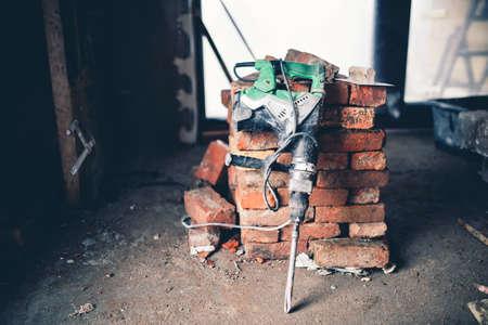 debris: Construction tool, industrial jackhammer with demolition debris and bricks