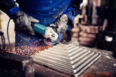 angle bar: industrial engineer working on cutting a metal and steel bar with angle grinder, metallurgic factory details Stock Photo