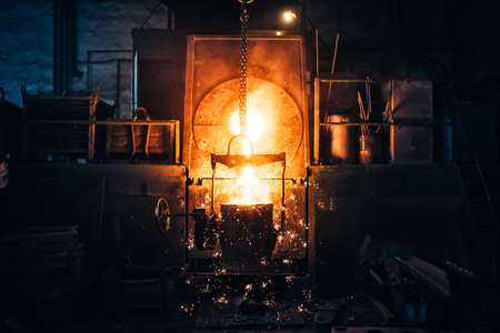 castings: Smelting metal in a metallurgical plant. Liquid iron from metal ladle pouring in castings at factory