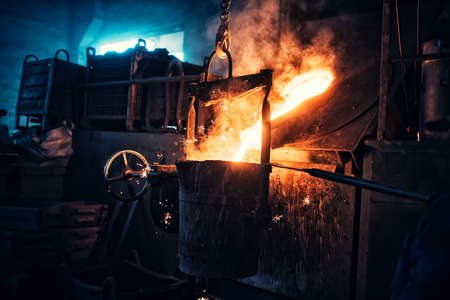 smelting plant: Liquid iron flowing in steelworks. Industrial details of metallurgic factory or plant. Details of smelting metal Stock Photo