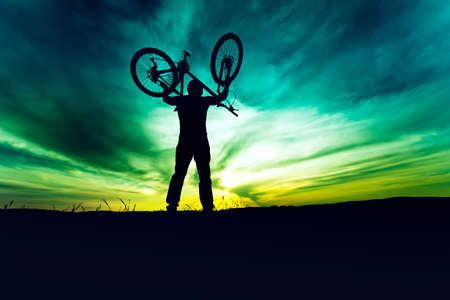 succesful: silhouette, contour of byciclist rising bike and celebrating. Action of succesful people winning contest Stock Photo