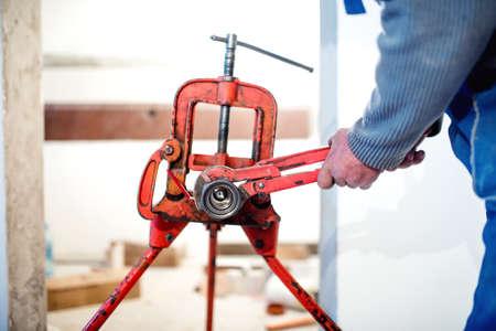adjusting: handyman plumber adjusting pipes with wrench