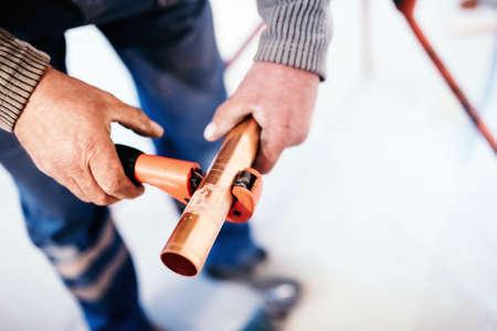 Industrial Loodgieter snijden van een koperen buis met een pijpsnijder. Stockfoto