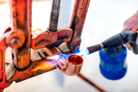soldering: industrial worker using propane gas torch for soldering copper pipes.
