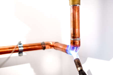 industrial plumber using blowtorch, propane gas torch for welding copper pipes