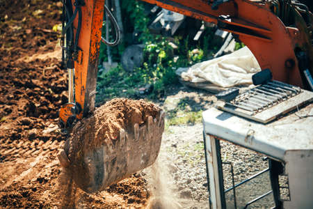 gravel pit: industrial excavator moving earth on construction site. Close-up of bucket full of earth Stock Photo