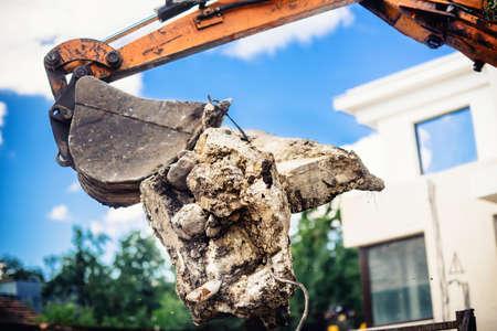 excavator on demolition site loading concrete blocks