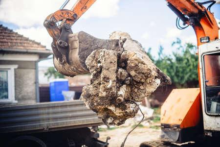 debris: hydraulic backhoe bulldozer loading demolition debris, stone and concrete for recycling Stock Photo
