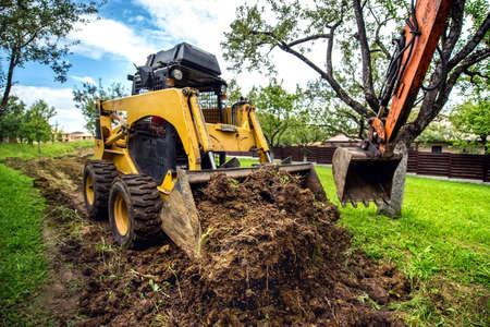 Gele mini bulldozer werken met aarde, bewegende bodem en het doen van landschapsarchitectuur werken