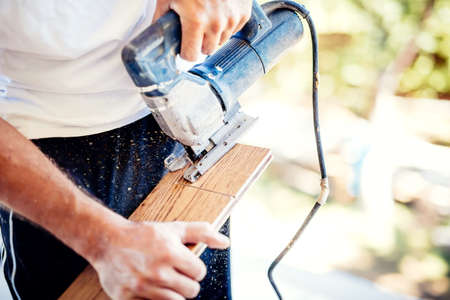male worker cutting wood parquet using circular saw during home improvement works Stock Photo