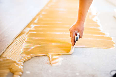 close-up of hand of worker adding glue during parquet installation Standard-Bild