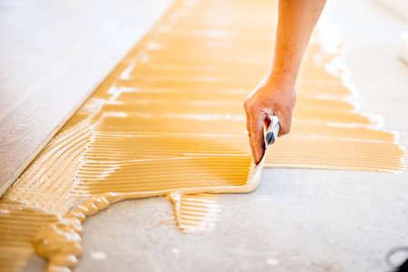 zblízka rukou pracovníka přidávání lepidla během instalace parket Reklamní fotografie