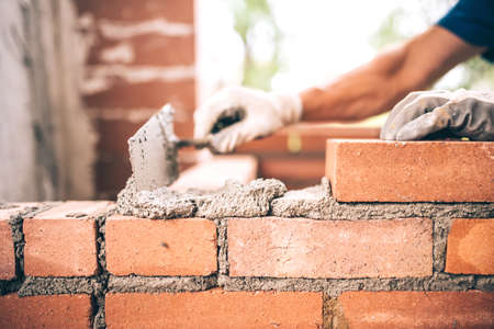 Bricklayer worker installing brick masonry on exterior wall with trowel putty knife Stok Fotoğraf - 60728329