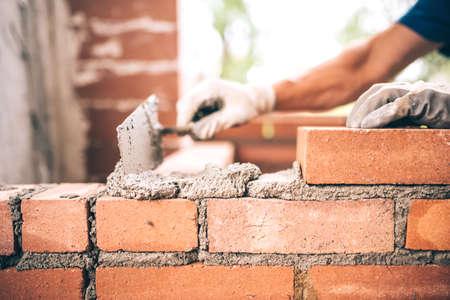 Briqueteur travailleur installation en maçonnerie de briques sur le mur extérieur avec un couteau à mastic truelle
