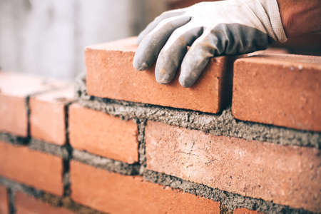 Close up of industrial bricklayer installing bricks on construction site 스톡 콘텐츠