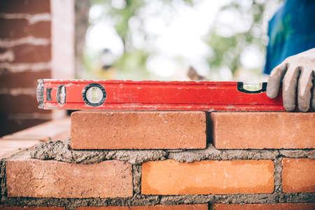 construction worker, bricklayer or mason laying bricks and creating walls. Detail of level tool Stockfoto