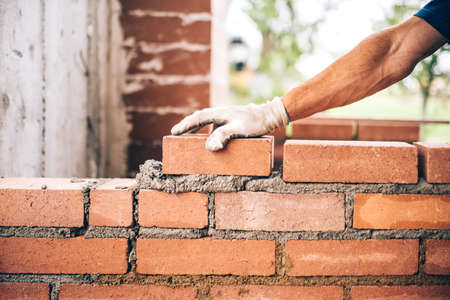 industrial bricklayer worker placing bricks on cement while building exterior walls, industry details Archivio Fotografico