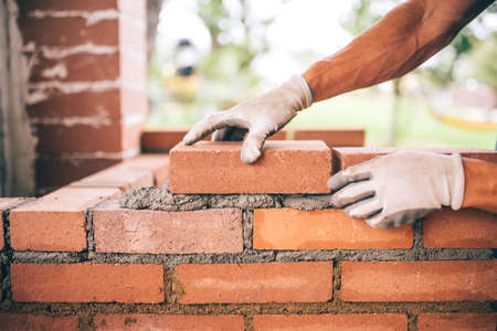 professional construction worker laying bricks and building barbecue in industrial site. Detail of hand adjusting bricks Standard-Bild
