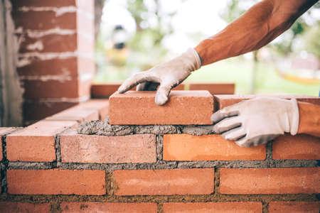 mortero: trabajador de la construcción profesional de la colocación de ladrillos y la construcción de barbacoa en el sitio industrial. Detalle de ajuste de mano ladrillos Foto de archivo