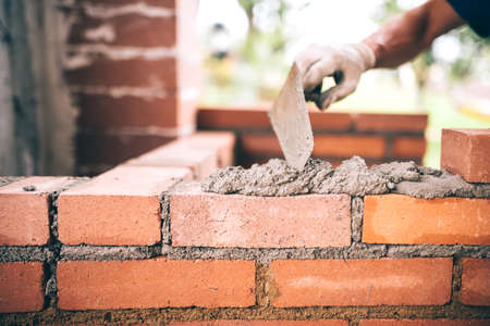 Industriële bouwmaker werkende muren met bakstenen, mortel en stopverfmes Stockfoto - 60728331
