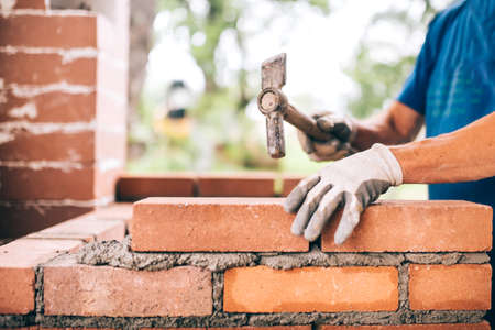 trabajador industrial la construcción de las paredes exteriores, que usa el martillo para la colocación de ladrillos en el cemento. Detalle del trabajador con las herramientas