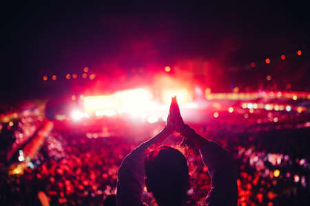 festival of lights: Silhouette of a young woman enjoying festival lights and concert. Woman making hand gestures at concert Stock Photo