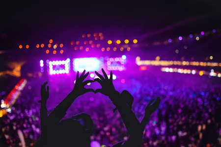 shaped hands: heart shaped hands showing love at festival. Silhouette against concert Lights background