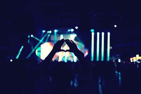heart hands: silhouette of happy woman enjoying music at live concert or festival Stock Photo