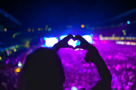 shaped hands: heart shaped hands at concert, woman at festival loving the artist and the music