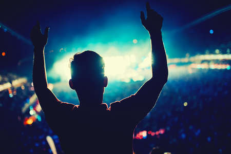 heart hands: Man at concert dancing against lights background. Silhouette of man at music festival